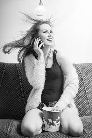 rubia: retrato de la joven señora rubia bonita divertirse viendo la televisión de la película con palomitas y hablando por teléfono móvil, excitado feliz sonriente sobre fondo claro espacio de la copia. Fotografía en blanco y negro
