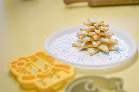 plastic christmas tree: Closeup picture of christmas cookies laying on white plate copy space