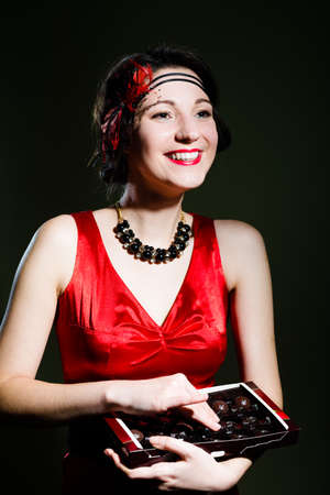silk screen: Portrait of pretty girl wearing silk evening dress holding box of chocolate sweets. Young woman in 20s styled red costume on black screen background.