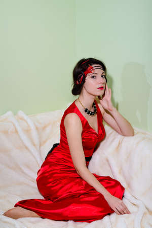 satin dress: Picture of charming girl wearing retro red dress sitting on fur rug. Young woman in 1920 styled costume on light green wall background.
