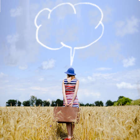 freedom of thought: Picture of young woman in hat holding old suitcase. Girl in striped dress standing in wheat field with thought bubble on sunny sky background.