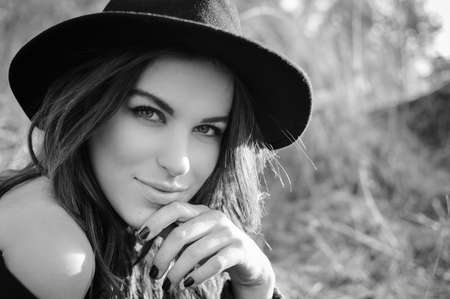 sensually: Portrait of beautiful elegant young lady in jacket having fun joyfully looking at camera and sensually smiling over outdoors background. Black and white closeup picture