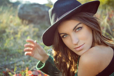 naked girl black hair: Portrait of charming girl in black hat and green sweater. Young woman with naked shoulder looking at camera on fall blurred countryside