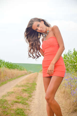 Picture of sexy beautiful girl wearing coral mini dress and fancy necklace. Young lady with tangled hair looking at camera on summer road countryside background.