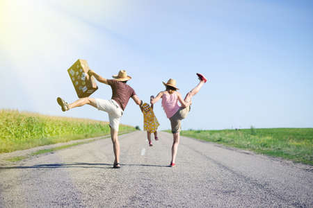 Picture of happy amazing family jumping and having fun on road in summer. Backview of exciting parents and baby girl with old suitcase on sunny countryside background.