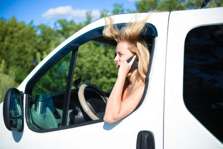 blowed: Picture of young girl with blowed hair in white car speaking by phone. Young woman talking with someone on sunny summer countryside background.