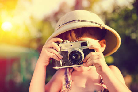 pith: Portrait of little boy making photo with vintage camera. Kid wearing pith helmet on sunny flared countryside background.