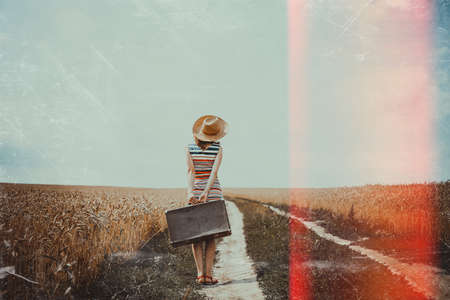 struck: Picture of young woman with retro suitcase standing on road in wheat field. Backview of girl in striped dress and straw hat on film light struck countryside background.