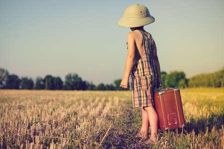 médula: Fotografía de un niño pequeño que desgasta sombrero de explorador y el mameluco de la tela escocesa grande que lleva valize en el campo. Niño en el sombrero del safari que mira hacia atrás en el cielo azul al aire libre fondo