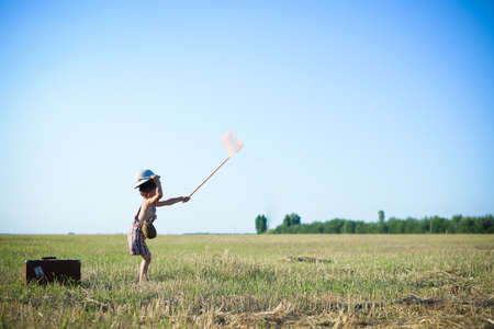 pith: Sweet little boy wearing pith helmet and plaid romper holding ring net in summer countryside. Sideview of kid in safari hat near old suitcase over blue sky background Stock Photo