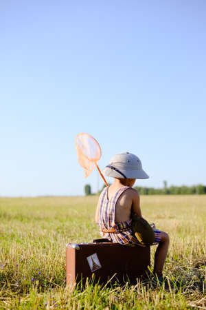 romper: Picture of little boy with ring net sitting on suitcase in summer countryside. Backview of kid in safari helmet relaxing on valize