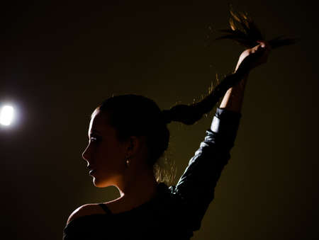 lady silhouette: Black silhouette of profile of professional dancer womans face. Pretty lady with long hair dancing in the midnight. Dancer holding her hair.