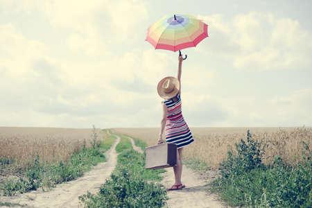 fin de semana: Mujer con la maleta de pie en la carretera entre el campo de trigo. Backview de la muchacha en el sombrero ascendente paraguas.