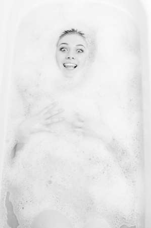 sensually: Picture of laying in the soap water beautiful young lady having fun sensually showing tongue and looking at camera on light copy space background. Black and white photography