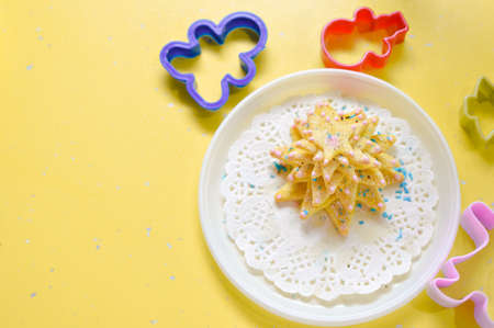 bickie: Image of hand made cake or cookies on white plate with molds around on yellow table background
