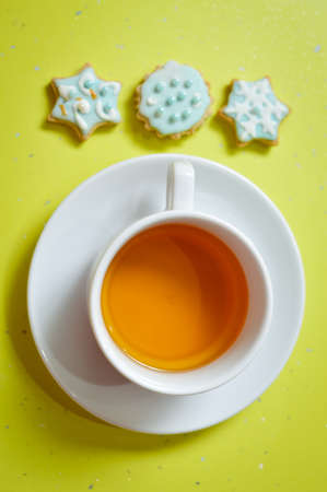 bickie: Close up image of three ginger cookies and cup of tea over light table background