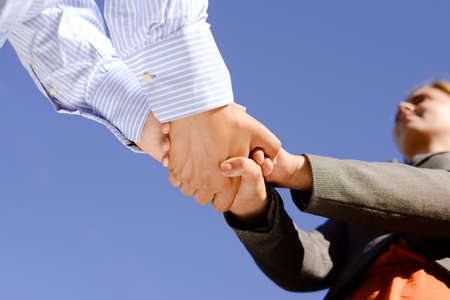 hand in hand: Closeup of man and women holding hands on blue sky background. Coworkers or happy couple in formal.