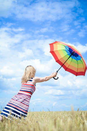 field stripped: Picture of beautiful blond woman flying away in the wheat field. Ladi in multi-coloured stripped dress holding umbrella.