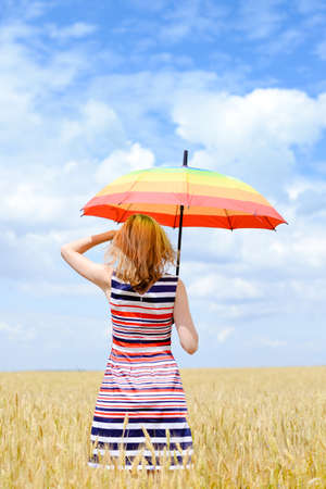 Blond lady holding umbrella and looking away. Female in stripped dress counting clouds and enjoying the sun. Stock Photo