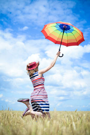 field stripped: Happy female in stripped dress and red hat jumping with rainbow umbrella in the wheat field on sunny blue sky outdoors background