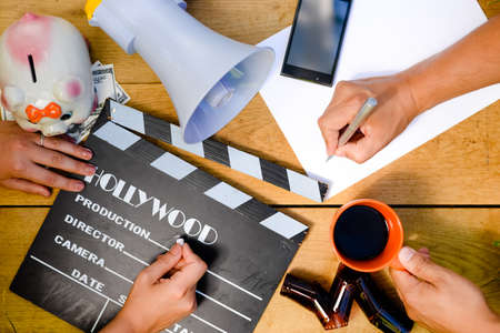 Two directors working in team. The following objects are organized on the wooden table: smart phone, movie clapper, rapid access film.