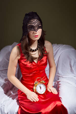 suspense: Picture of young beautiful female in black lace mask holding retro alarm clock on knees. Its almost midnight and mysterious lady in red dress waiting on blurred indoor background. Stock Photo
