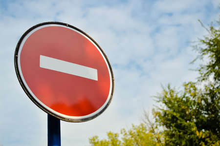 banning the symbol: Picture of road sign stop standing somewhere in summer. Red circle with white brick on blue sky outside background.