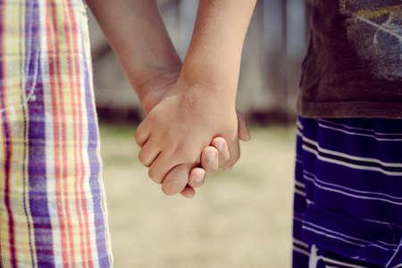 niño de pie: Imagen de dos manos del niño que sostienen entre sí. Primer plano de los mejores amigos símbolo en el fondo fuera borrosa verano.