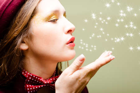 flying kiss: Picture of elegant beautiful girl in hat and bow tie sending air kiss. Side view of young pretty lady with flying lights on olivine abstract background.