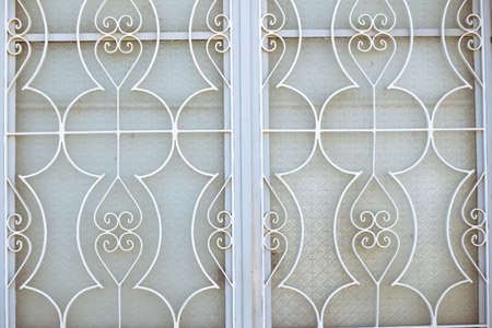 window grill: Picture of white metallick window grid. Artistic decoration detail on sunlight outdoor background.