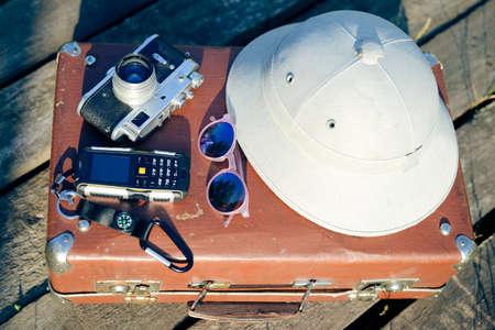 m�dula: Viajes de fondo con salacot, c�mara, gafas de sol y el tel�fono celular en la parte superior de la maleta retro. Concepto Exploraci�n