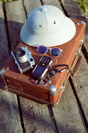 médula: Viajes de fondo con salacot, cámara, gafas de sol y el teléfono celular en la parte superior de la maleta retro. Concepto Exploración