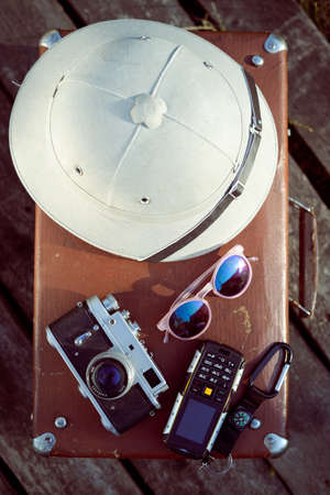 pith: Travel background with pith helmet, camera, sunglasses and cellphone on top of retro suitcase. Exploration concept