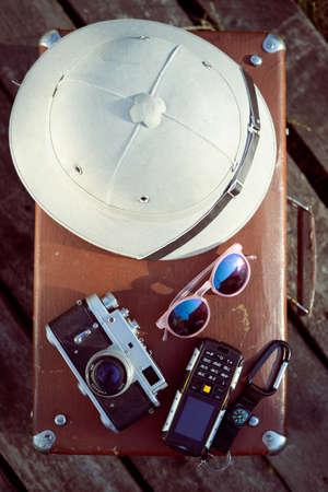 pith: Viajes de fondo con salacot, c�mara, gafas de sol y el tel�fono celular en la parte superior de la maleta retro. Concepto Exploraci�n