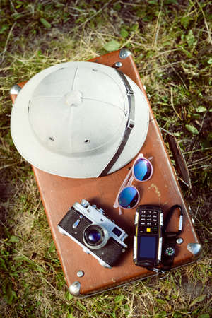 médula: Vista superior de PithHelmet blanco, cámara vieja, teléfono móvil y gafas de sol en la maleta retro.