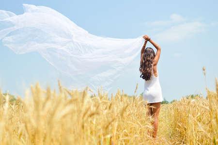 viento: Imagen alegre romántica hermosa dama joven con tela ligera y disfrutar al aire libre mirando a lo largo de campo de trigo y cielo azul copia espacio fondo
