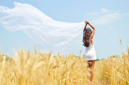 Picture of joyful romantic beautiful young lady holding light fabric and enjoying outdoors looking up over wheat field and blue sky copy space background