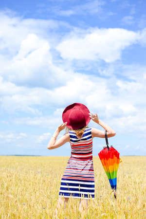 sunny day: Rom�ntico elegante dama divertirse sosteniendo paraguas del arco iris en un d�a soleado cielo azul de fondo al aire libre campo