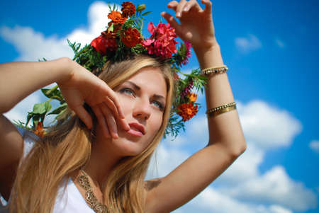 manos levantadas al cielo: Portrait of beautiful young lady in flower wreath and necklace. Closeup of charming girl with raised hands on bright blue sky background.
