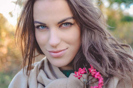 gently: Portrait of beautiful young female in warm shawl holding pink wildflowers. Pretty girl gently smiling on autumn blurred outdoor background.