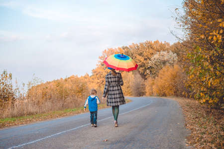 Picture of woman with rainbow umbrella walking with little boy on autumn countryside road. Backview of happy family on golden trees outdoor background. Standard-Bild