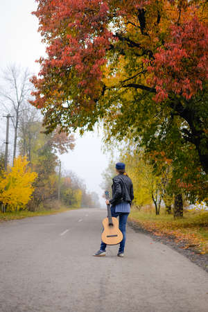 bard: Picture of beautiful young lady in hat with guitar waiting on countryside road. Backview of pretty girl wearing black jacket and jeans on colorful autumn outdoor background.