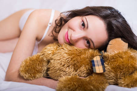 gently: Portrait of beautiful exciting young female in white underwear lying with teddy bear. Charming girl gently smiling on blurred bedroom background.