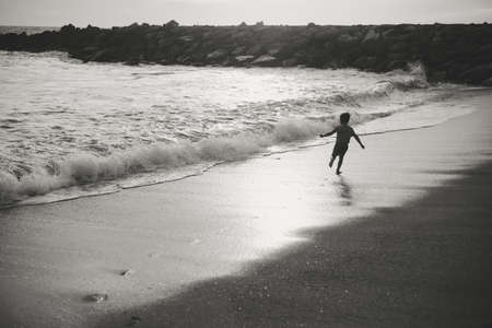 exciting: Picture of exciting little child running on seashore beside waves. Black and white image of kid in front of swash on seaside background.