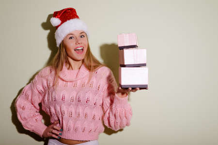 exciting: Portrait of exciting beautiful young woman in Santa hat holding three pink presents. Pretty girl in short pink sweater excited on beige indoor background.