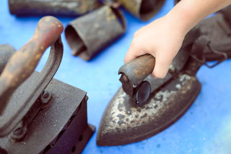 vintage objects: Picture of hand holding old rusty iron. Collection of vintage obsolete objects on blue indoor background.