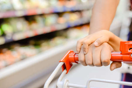 Picture of shopping cart pulling by woman and kid's hands. Part view of happy family beside store display on blurred indoor background.