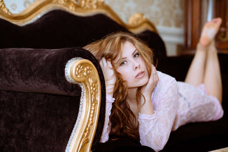 velvet dress: Portrait of beautiful young lady lying on rich velvet luxury sofa. Sexy girl in lace dress on aristocratic apartment background.