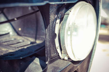 car grill: Picture of round car headlight on black grill. Old retro auto detail on blurred outdoor background.