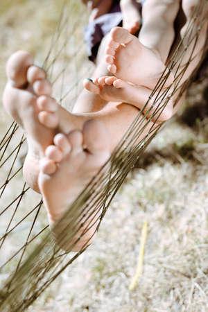 niño y niña: Cuadro del hombre y pequeño niño descalzo descansando en el campo. Primer plano de los pies de la familia feliz en hamaca en día soleado de verano, de fondo.